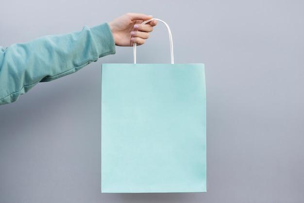Hand die een het winkelen papieren zak houdt Premium Foto