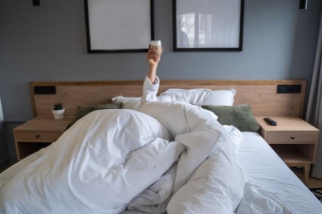 Hand die een kop van koffie thuis in bed houdt Gratis Foto