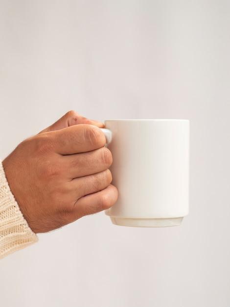 Hand die een mokmodel houdt Gratis Foto