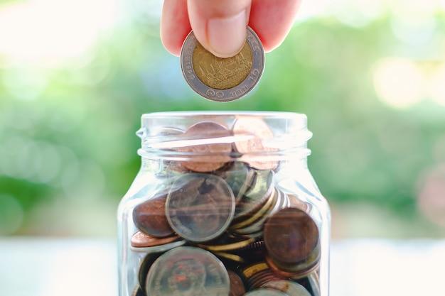 Hand die een muntstuk in de glaskruik spaart Premium Foto