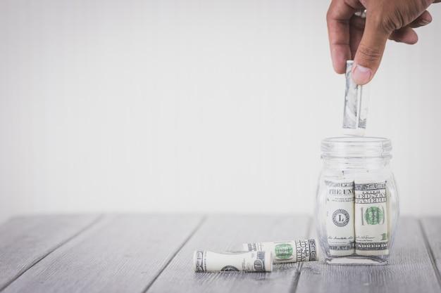 Hand die gelddollars in glasfles zet, concept besparingsgeld, handelsinvesteringen Premium Foto