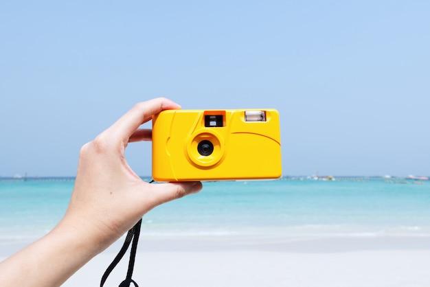 Hand die gele camera op de achtergrond van het de zomerstrand houden Premium Foto
