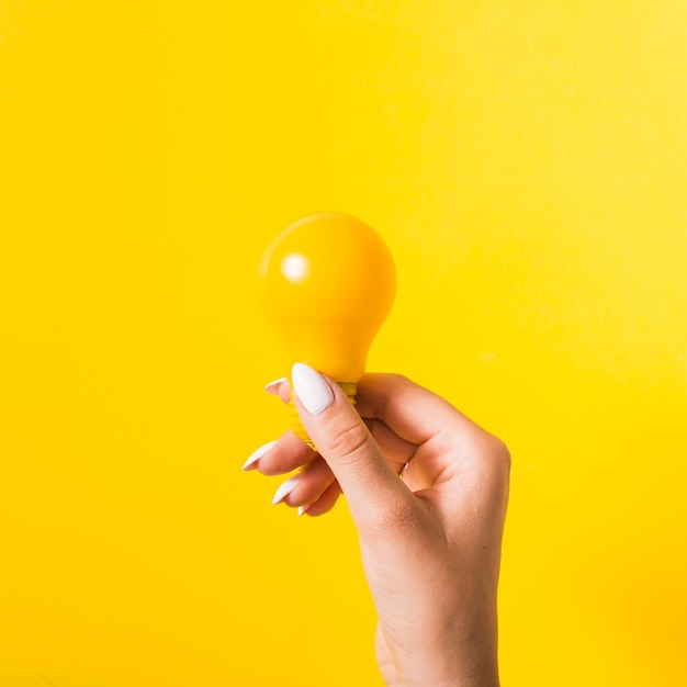Hand die gele gloeilamp houdt tegen gekleurde achtergrond Gratis Foto