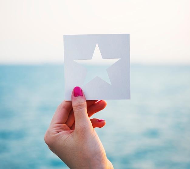 Hand die geperforeerde document stervorm met oceaanachtergrond houdt Gratis Foto