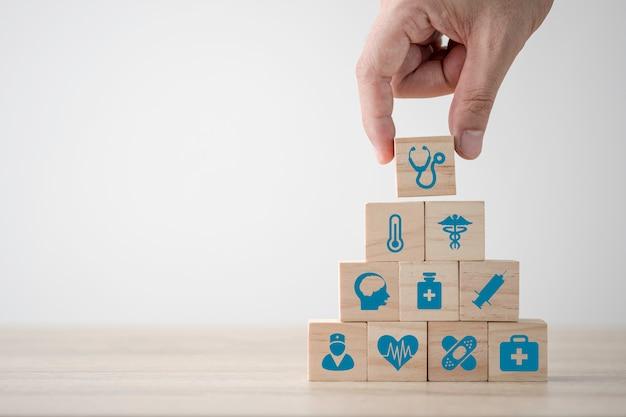 Hand die gezondheidszorggeneeskunde en het ziekenhuispictogram stapelen dat het scherm op houten kubussen op lijst drukte. zorgverzekeringen en investeringen. ruimte concept kopiëren. Premium Foto