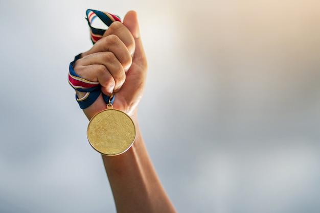 Hand die gouden medaille op hemel houdt Premium Foto