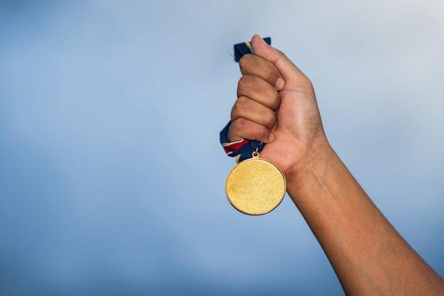Hand die gouden medaille tegen bewolkte hemel houdt Premium Foto