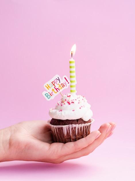Hand die heerlijke muffin met gelukkig verjaardagsteken houdt Gratis Foto