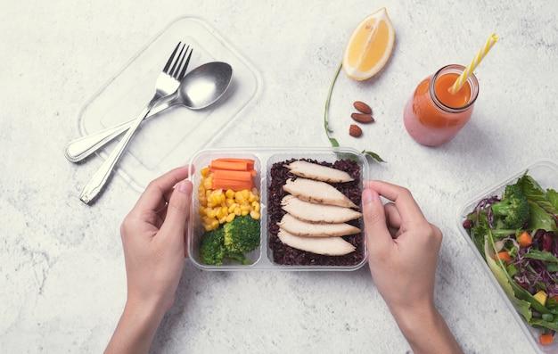 Hand die het verse vakje van de gezonde voedinglunch met plantaardige salade op lijst houden. Premium Foto