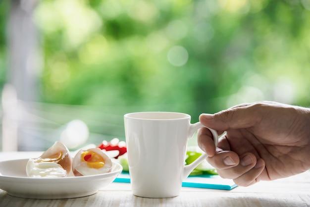 Hand die hete kop koffie met gekookte eieren met verse komkommer aardappel ui salade ontbijten set met groen bos - ontbijt eten concept Gratis Foto