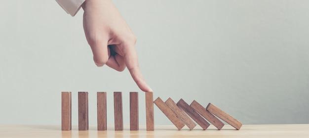 Hand die houten domino bedrijfscrisiseffect of concept van de risicobescherming tegenhoudt Premium Foto