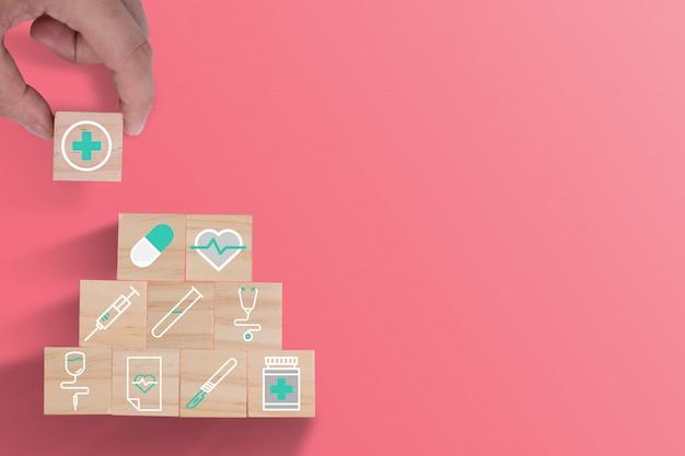 Hand die houten kubussen het stapelen van gezondheidszorggeneeskunde en het ziekenhuispictogram op mooie roze achtergrond zetten. zorgverzekeringen en investeringen. Premium Foto