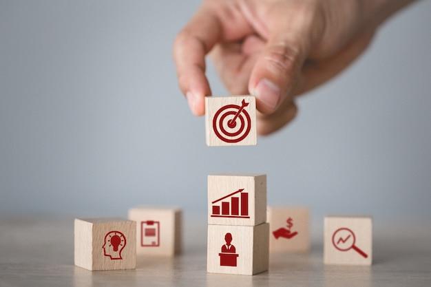 Hand die houtsnede schikken die met pictogrampijl en zaken stapelen, die het bedrijfsconcept richten. Premium Foto