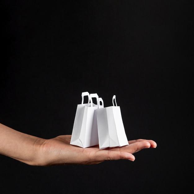 Hand die kleine witte zakken houdt Gratis Foto