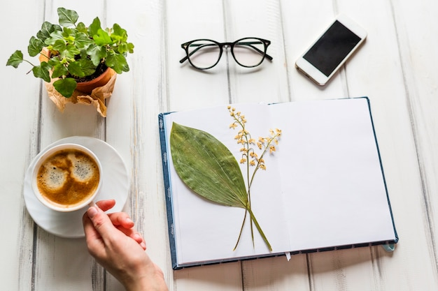 Hand die koffie op creatieve werkplaats neemt Gratis Foto