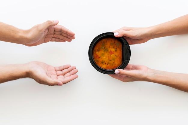 Hand die kom soep geeft aan behoeftige Premium Foto