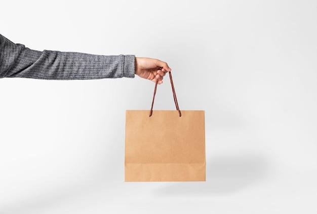 Hand die lege pakpapierzak voor modelmalplaatje houden die en op grijze achtergrond adverteren brandmerken. Premium Foto