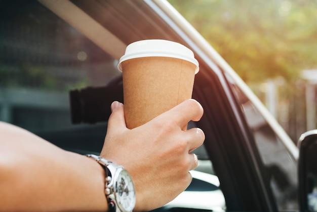 Hand die meeneemkoffie in een auto houdt Gratis Foto