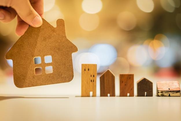 Hand die mini houten huismodel kiest van model op houten tafel, Premium Foto