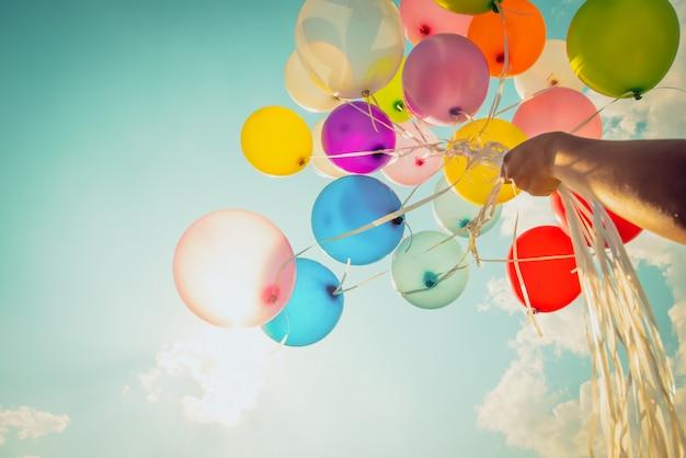 Hand die multi gekleurde ballons houdt die met een retro uitstekend effect van de instagramfilter worden gedaan. Premium Foto