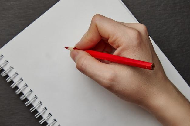 Hand die op notitieboekje met potlood schrijft Premium Foto