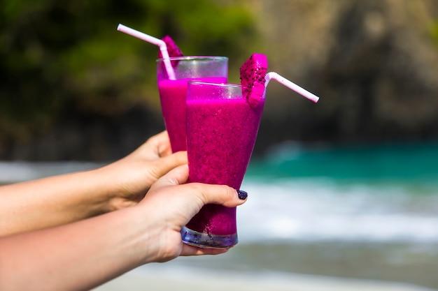 Hand die purpere cocktail in glas houdt dat met plastic stro en stuk van draakfruit wordt verfraaid op het zandige tropische strand Premium Foto