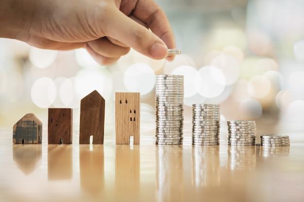 Hand die rij van muntstukgeld op houten lijst en mini houten huis kiest, Premium Foto