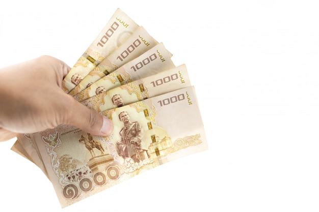 Hand die thaise bankbiljetten vijfduizend baht houden die op witte achtergrond worden geïsoleerd. Premium Foto
