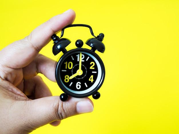 Hand die uitstekende zwarte wekker op gele achtergrond houdt Premium Foto