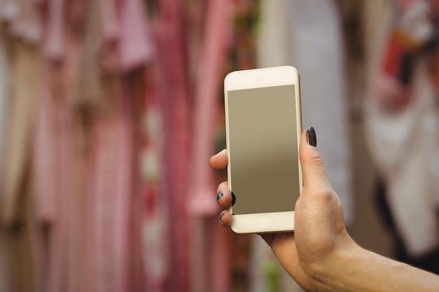 Hand die van vrouw mobiele telefoon houdt Gratis Foto