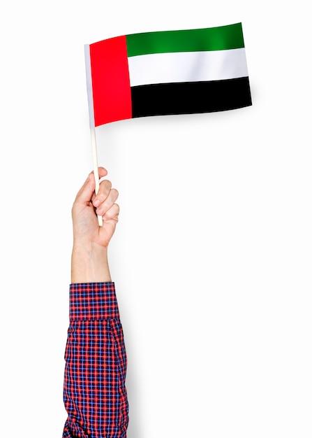 Hand die vlag van verenigde arabische emiraten toont Gratis Foto