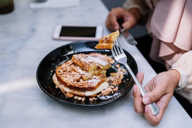 Hand die vork gebruiken om te dobbelen franse toost van de zwarte schotel op lijst met vage achtergrond van wijfje. Premium Foto