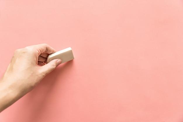 Hand die wit rubber voor het wissen van iets op lege roze achtergrond houdt. abstracte achtergrond met kopie ruimte. Premium Foto