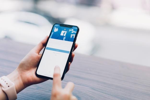 Hand drukt op het facebook-scherm op apple iphone x, sociale media. Premium Foto