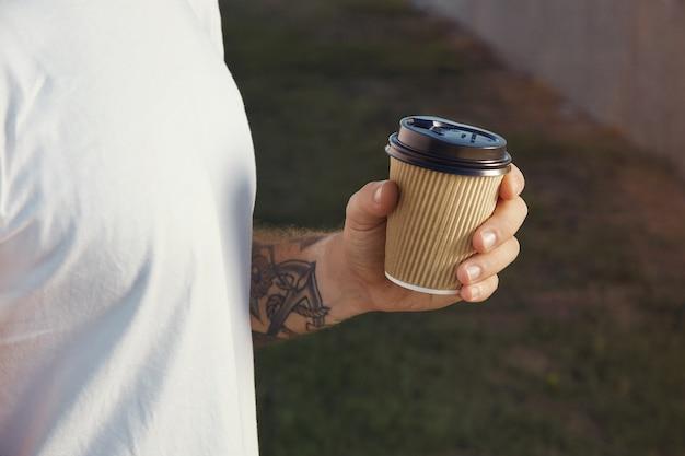 Hand en borst van een witte getatoeëerde man met een wit t-shirt zonder label met een lichtbruine papieren koffiekop Gratis Foto