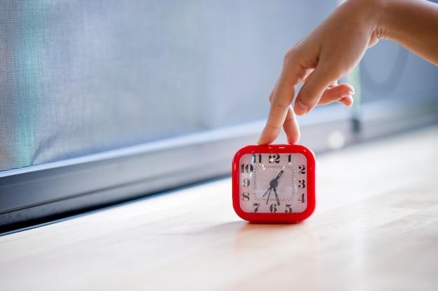 Hand en rode wekker die het alarm laat zien elke ochtend, het concept van stiptheid Premium Foto