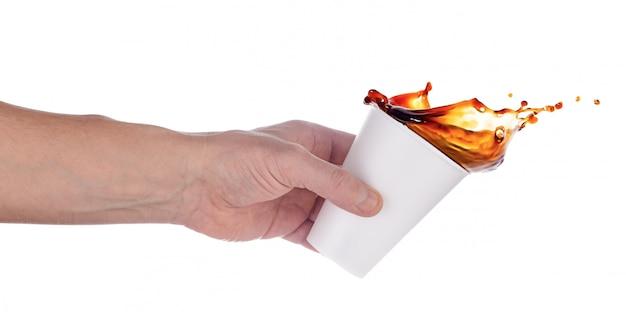 Hand gieten koffie of cola uit witte plastic beker Premium Foto