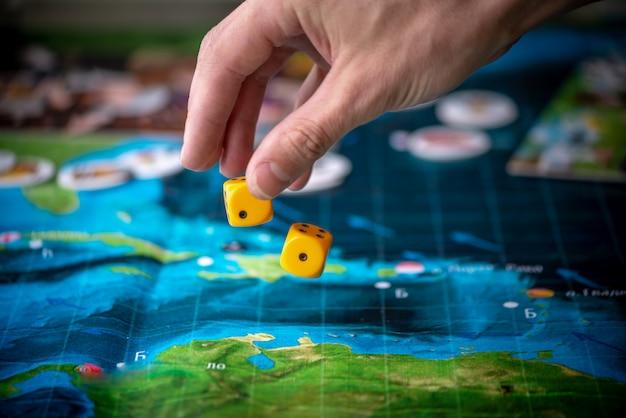 Hand gooit twee gele dobbelstenen op het speelveld. speelmomenten in dynamiek. geluk en opwinding. strategie voor bordspellen Premium Foto