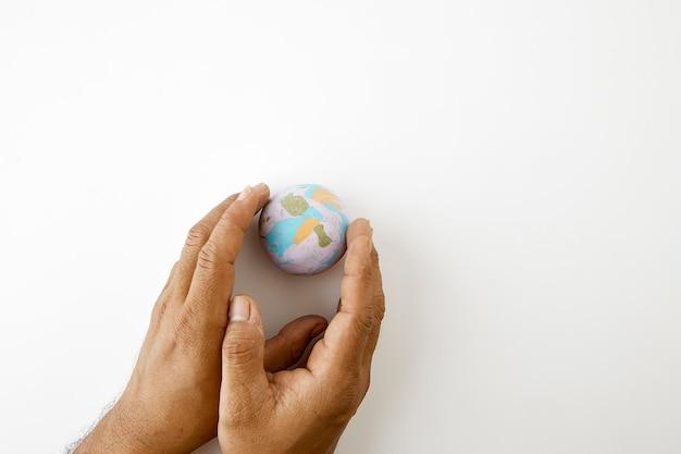 Hand houd plastiline symbool van de planeet aarde bol Premium Foto