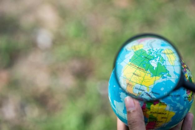 Hand houden earth globe en vergrootglas boven de amerika, elementen van deze afbeelding ingericht b Premium Foto