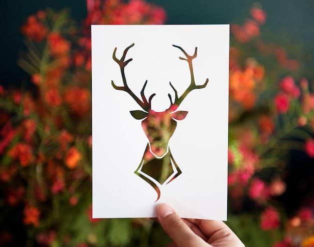Hand houden herten met geweien papier snijwerk Gratis Foto