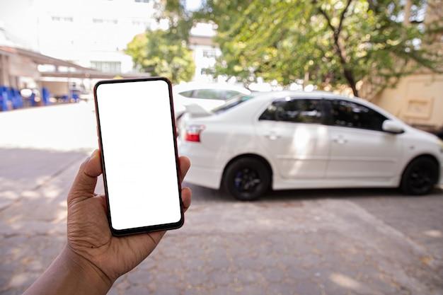 Hand houden leeg scherm op mobiel, mobiel, tablet op wazige witte auto. Premium Foto