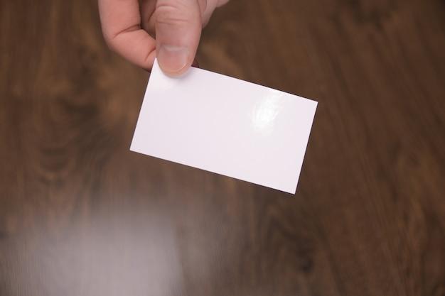 Hand houden lege witte kaart mockup met afgeronde hoeken. duidelijke telefoonkaart mock-up sjabloon met arm. voorkant van plastic visitekaartje. controleer het ontwerp van de offsetkaart. zakelijke branding. Premium Foto