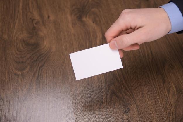 Hand houden lege witte kaart mockup met afgeronde hoeken. voorkant van plastic visitekaartje. controleer het ontwerp van de offsetkaart. zakelijke branding. Premium Foto