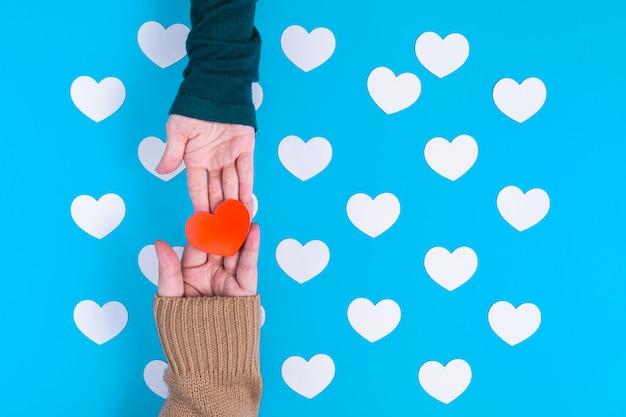 Hand houdt een rood hart vast aan de hand van iemand, die zijn over een groep witte harten geplaatst op blauw Premium Foto