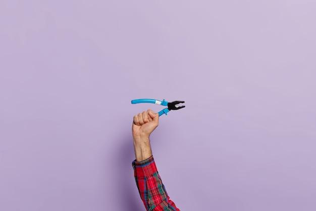 Hand houdt tang met blauwe plastic handvatten voor constructie en reparatie Gratis Foto