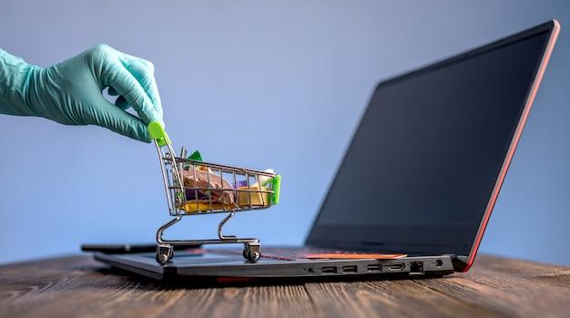 Hand in een steriele handschoen houdt een winkelwagentje met een creditcard. aankopen via internet tijdens de pandemie van het coronavirus Premium Foto