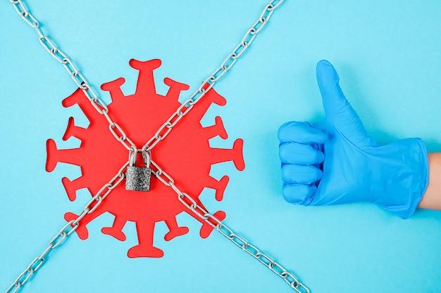 Hand in medische handschoenshows als gebaar en rood coronavirus, virus, bacterie, microbe achter kettingen en gesloten slot Premium Foto