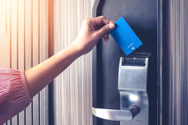 Hand invoegen sleutelhanger om een deurbeveiligingsverificatie te ontgrendelen in de hotel- of appartementbeveiliging Premium Foto