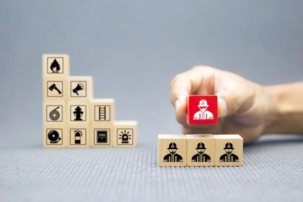 Hand kiezen houten blok met firefighter pictogram. Premium Foto